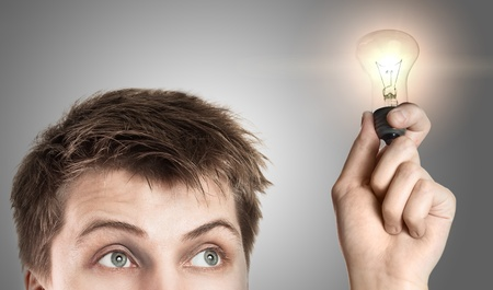 smart man: Funny young man with light bulb, on gray background  Stock Photo