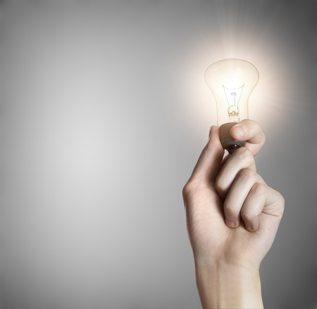 Glowing lightbulb in a hand on gray background with copyspace