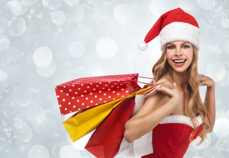 Charming woman in santa costume holding a shopping bags over winter background  Stock Photo - 12638669