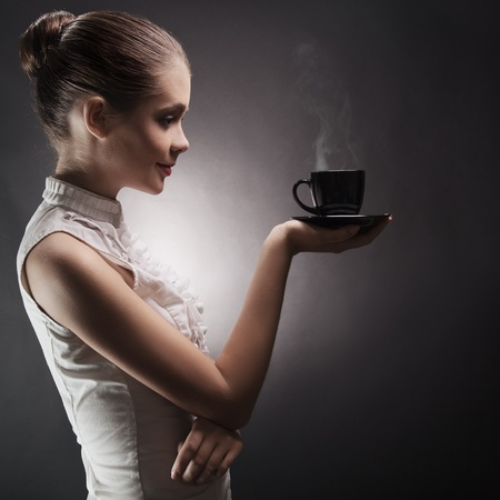 Attractive woman with an aromatic coffee in hands  photo