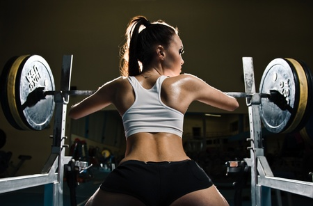 powerlifting: Sporty sexy woman in gym