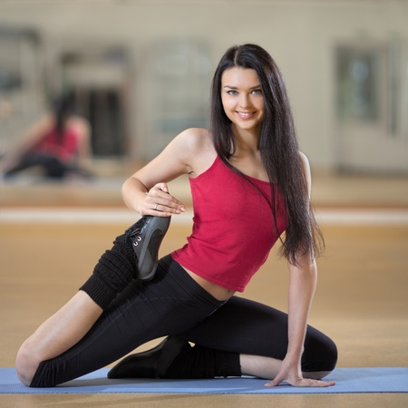 Portrait of healthy young woman practicing yoga on exercising mat  photo