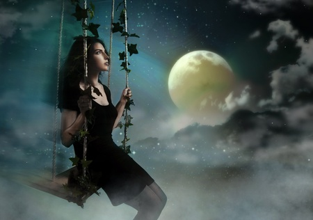 witch face: Beauty brunette swinging in night heaven