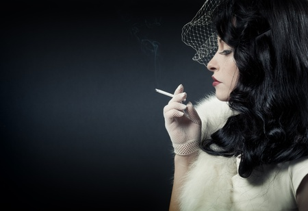 Retro woman smoking on dark background  photo