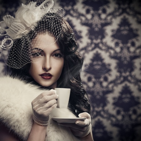 Young beautiful retro lady drinking coffee  photo
