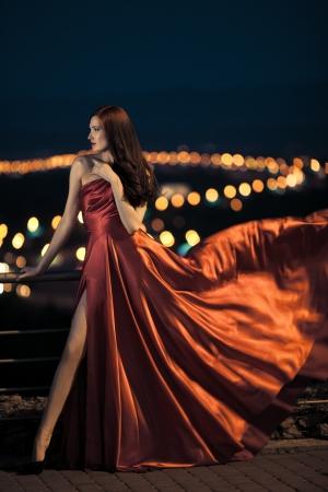 donna ricca: Sexy bellezza giovane donna in abito rosso svolazzante