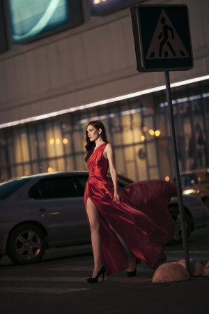 Sexy beauty woman in fluttering red dress - motion shot photo