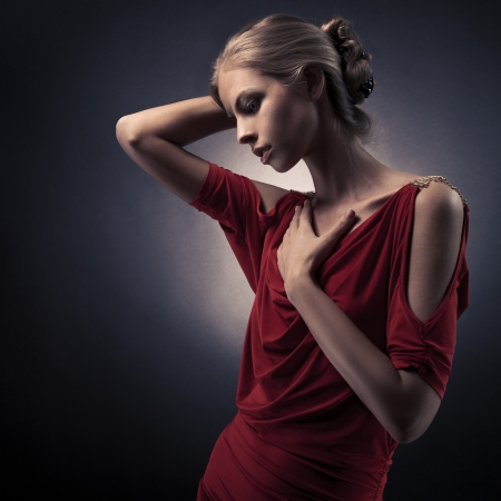 Young beautiful woman in red dress on the dark background in the studio