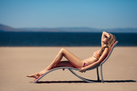 deckchair: Beautiful woman lying on a deckchair at the beach  Stock Photo