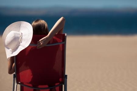 woman lying on a deckchair at the beach  photo