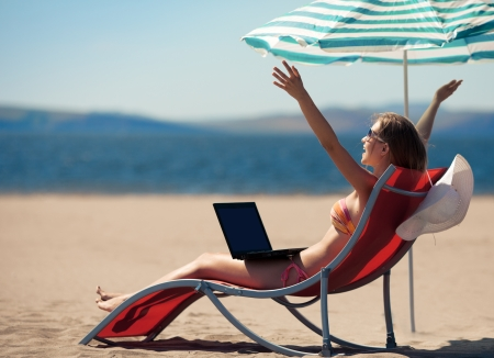 palm computer: sexy woman works near the sea  Stock Photo