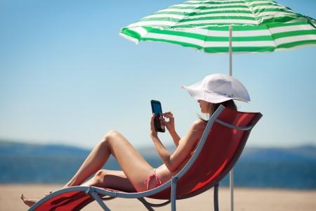 strandstoel: Vrouw die tablet-computer zittend op het strand in ligstoel en dat zonbad