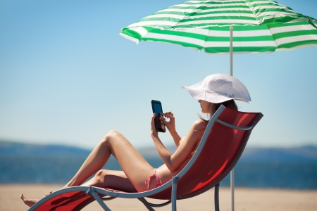 Woman holding tablet computer sitting on the beach in deck chair and taking sun bath  Stock Photo