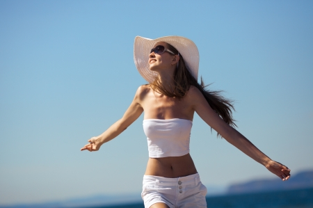 bliss: Happiness bliss freedom concept. Woman happy smiling joyful with arms up dancing on beach in summer during holidays travel.
