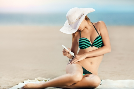 Portrait of woman taking skincare with sunscreen lotion at beach  photo