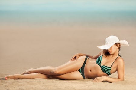 sensuous: Bright photo of a beautiful model relaxing on a beach. Room for text