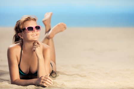 bliss: Bright photo of a beautiful model relaxing on a beach. Room for text