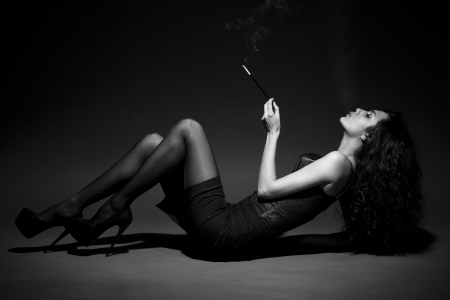 woman smokes in the dark. studio shot. space for text. BW Image photo