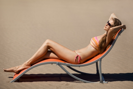 sunbathing: Beautiful woman lying on a deckchair at the beach  Stock Photo