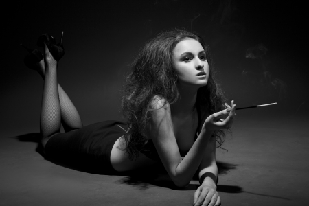 woman smokes in the dark. studio shot.  BW Image  photo