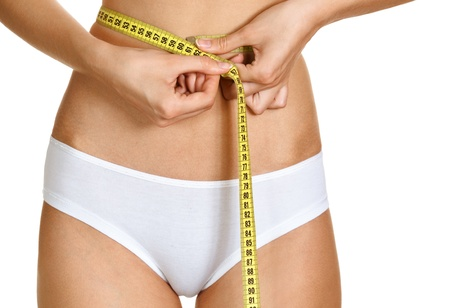 conscious: Portrait of young conscious woman measuring her waist over white background  Stock Photo