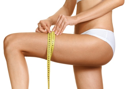 Diet - young woman is measuring her thigh with measuring tape Stock Photo - 14852740