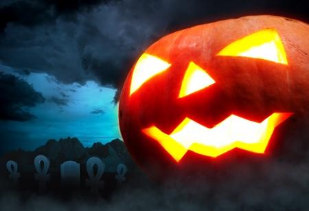 samhain: Decoraci�n de Halloween - un cementerio con una calabaza en la noche Foto de archivo