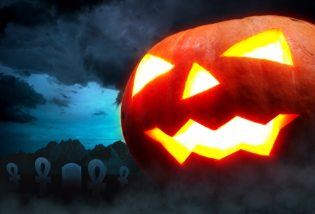 samhain: Halloween decoration - a graveyard with a pumpkin in the night  Stock Photo