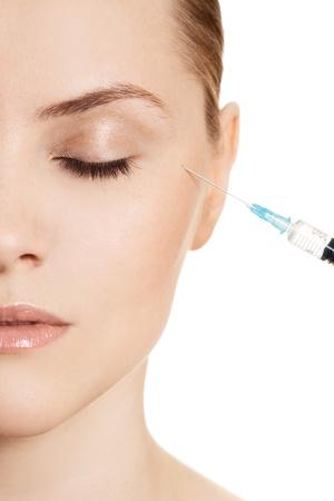 Hermosa mujer recibe una inyecci�n en la cara aislado en blanco