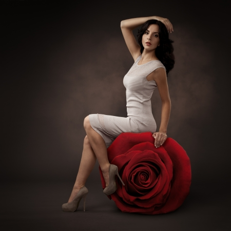 Elegant Beautiful Woman And Big Red Rose On Dark Background photo