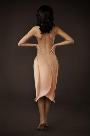 Elegant Beautiful Woman In A Flower Dress On Dark Background photo