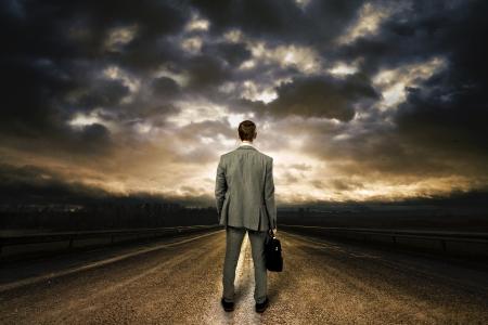 hombre solo: Hombre de negocios de pie en medio de la carretera. Dramático cielo arriba