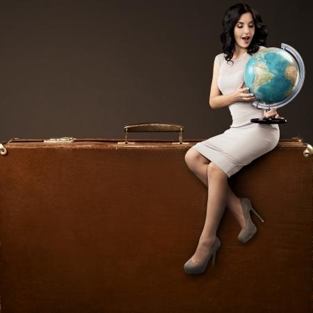 agence de voyage: Femme Belle Avec Globe En Mains Assis Sur Valise Rétro énorme. Espace pour le texte Banque d'images