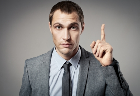 criticising: Young businessman criticizing on gray background