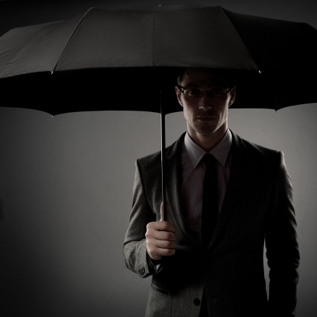Businessman in costume holding black umbrella photo