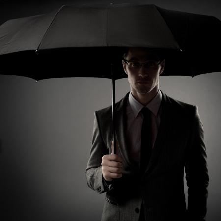 espionage: Businessman in costume holding black umbrella