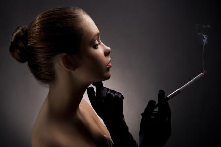 Beautiful smoking woman on dark background photo