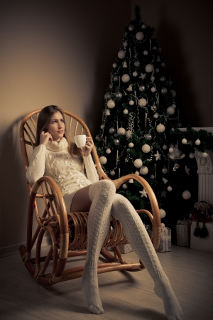christmas stocking: Beautiful woman with cup of coffee in chair. Christmas  decoration