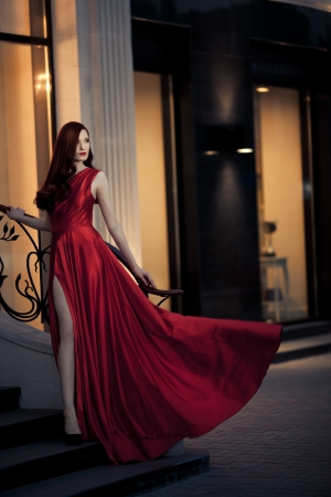 divas: Young Beauty Famous Woman In Red Dress Outdoor Stock Photo