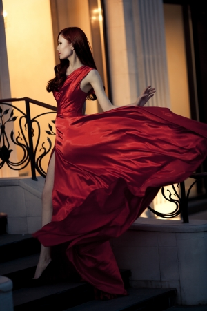 fluttering: Young Beauty Famous Woman In Red Dress Outdoor Stock Photo