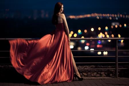 ライフスタイル: ひらひら屋外の赤いドレスの若い美しさの有名な女性 写真素材