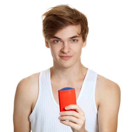 Close up portrait of young handsome man holding deodorant in hand. Isolated on white  photo