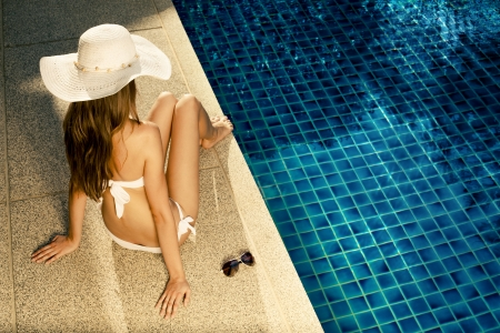 Beautiful woman sunbathing near swimming pool photo