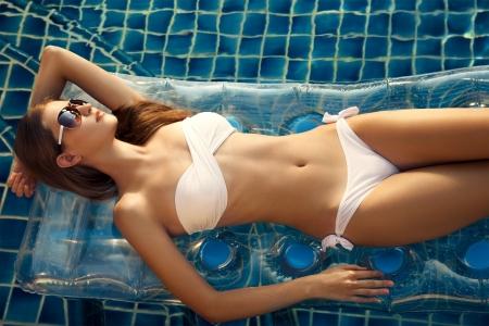 Hermosa mujer tomando el sol en la piscina