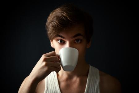 man drinking coffee on dark  background photo