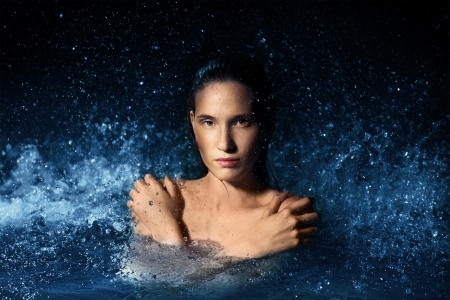 Beautiful woman in a spray of water photo
