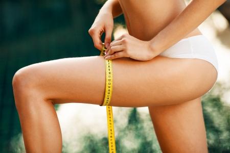 허리의 잘룩 한 선: 여자가 그녀의 허리를 측정. 퍼펙트 슬림 바디. 야외