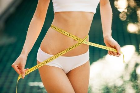 허리의 잘룩 한 선: 그녀의 허리를 측정하는 여자. 퍼펙트 슬림 바디. 옥외 스톡 사진