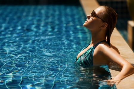 Portrait of young attractive woman having good time in swimming pool  photo