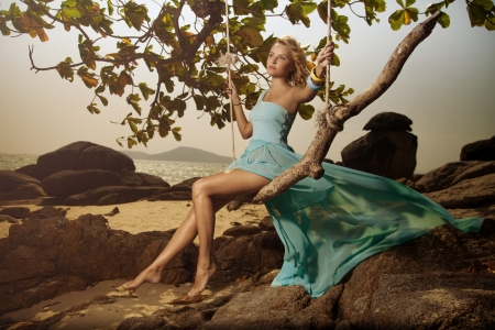 Beautiful Woman In Blue Fluttering Dress Swinging On A Beach Swing photo